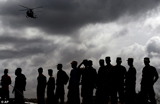 Daily Mail, May 25, 2009 Military and local people watch as a UN helicopter lands at the camp