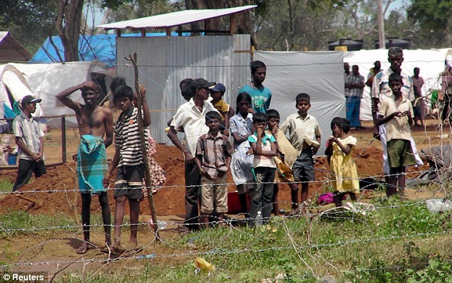 Daily Mail May 25, 2009 Victims of war: Tamil civilians stand behind a barbed-wire fence as they watch U.N. Secretary-General Ban Ki-moon tour their refugee camp