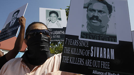 A member of the press holds a photo of Sri Lankan journalist Dharmeratnam Sivaram at a protest in 2013. Sivaram was abducted in April 2005 and found dead the next day. (Reuters/Dinuka Liyanawatte)